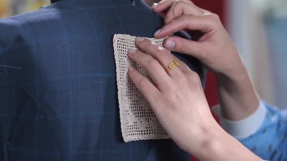 Thumbnail for Dressmaker's Hands Pinning Lace Decor To Dress