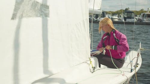 A Beautiful Girl Pulls Ropes on a White Sailing Yacht Before Leaving the Marina