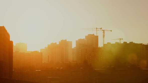 Cover Image for Construction Site in Warm Sunrise Light, Tower Cranes Working on Residential Building Morning Time