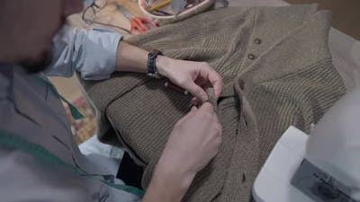 Top View of Male Tailor Sewing Button on Knitted Jacket
