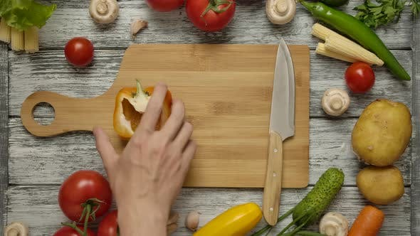 Thumbnail for A Human Hand Taking Half an Orange Paprika From a Cutting Board.