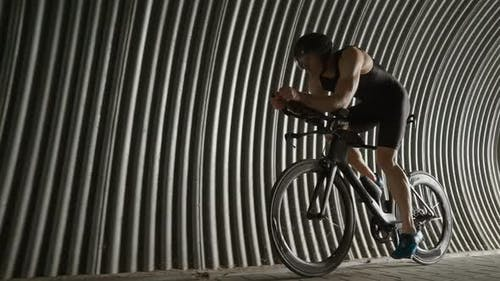 Pro Rider Rides a Cutting Bike Cyclist Rides in a Tunnel Athlete Training for Race  Slow Motion