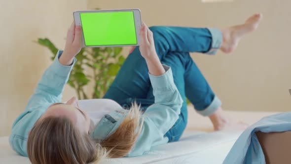Thumbnail for A Woman Lying on a Bed Using a Digital Tablet with a Green Screen