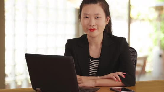 Thumbnail for Young business woman working with laptop computer and smartphone in home office
