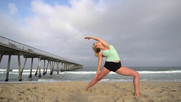 A young attractive woman doing yoga on the beach next to a pier.