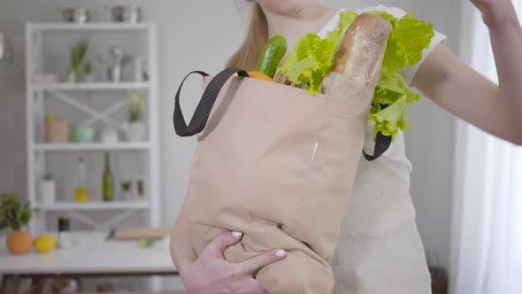 Thumbnail for Unbekannte Kaukasische Frau hält Einkaufstasche mit frischen Salatblättern, Brot und Früchten