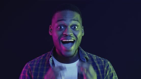 Close Up Portrait of Emotional African American Guy Touching Cheeks in Amazement Neon Lights