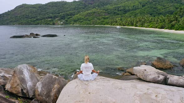Thumbnail for Aerial Fly Over Blonde Tanned Girl Sitting in Yoga Pose and Meditating on Granite Rock Against