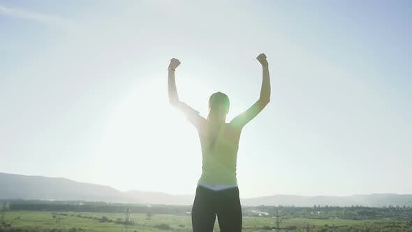 Cover Image for Young Sports Female Standing on the Edge of the Cliff Raising Her Hands Up