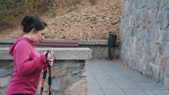 Thumbnail for Young attractive woman with nordic poles going up the stairs doing cardio training. Nordic Walking