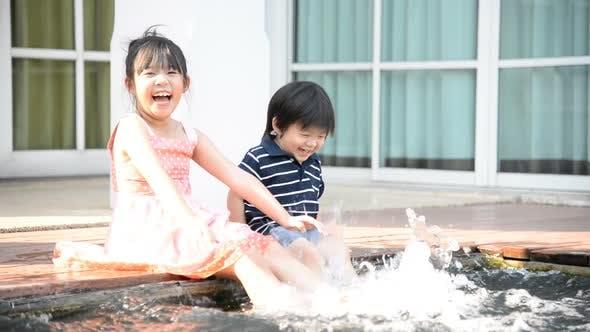 Asiatische Kinder planschen im Pool