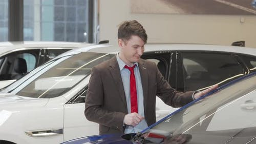 Mature Male Customer Examining Modern Automobile for Sale at the Dealership