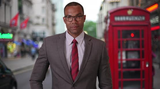 African corporate professional looking at camera with pride in London street
