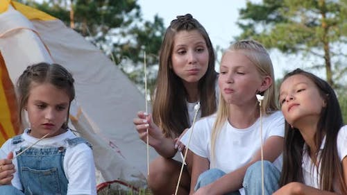 Adorable Little Girls Eating Fried Marshmallows in the Park Outdoors