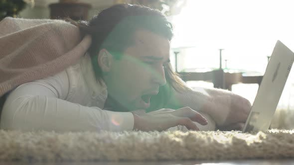 Thumbnail for Attractive Young Guy Yawns Lying on the Floor Covered with a Rug