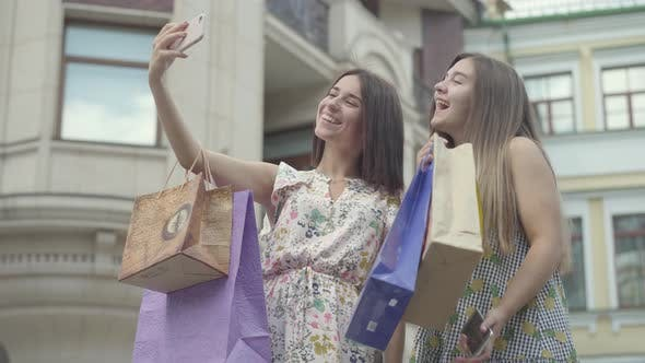 Thumbnail for Two Happy Girlfriends After Shopping with Shopping Bags Taking Selfie on Cellphone Outdoors