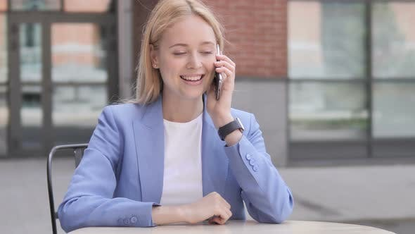 Thumbnail for Young Businesswoman Talking on Phone Sitting Outdoor