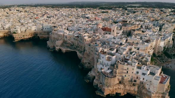 Flying Over Rooftops of Italian City of Polignano a Mare at Sunset, Apulia