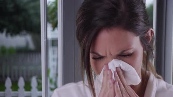 Thumbnail for Female with cold or allergies wiping nose with tissue inside house by window