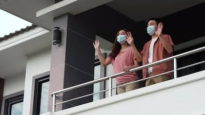 quarantine couple wearing a face mask and greeting neighbors from balcony of the home