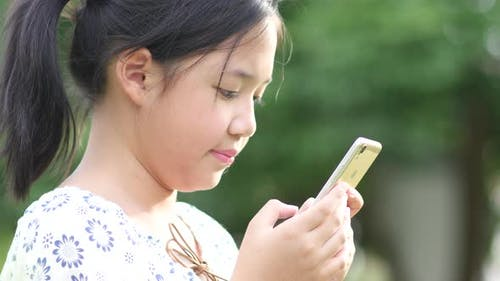 Beautiful Asian Girl Using The Smartphone With Feeling Relax And Smiley Face