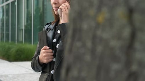 Smiling Student Talking to the Smartphone Near the University