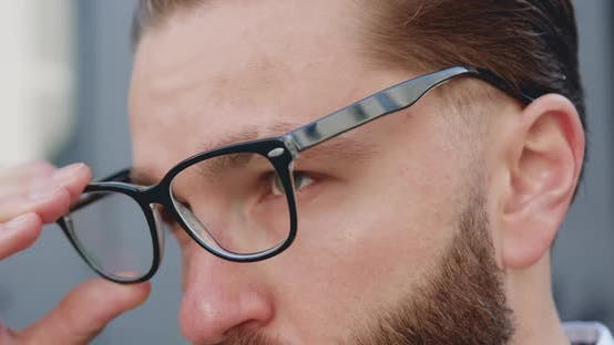 Thumbnail for Man with Green Eyes Which Putting on His Glasses and Looking Into the Distance