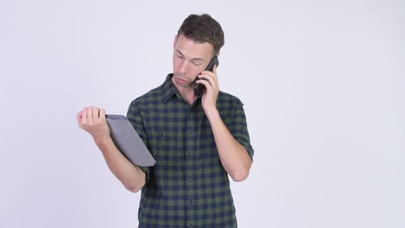 Thumbnail for Studio Shot of Happy Hipster Man Talking on Phone and Using Digital Tablet