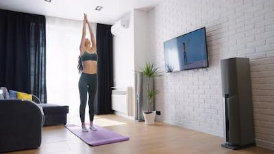 Woman Watching Online Tutorial and Doing Sports at Home