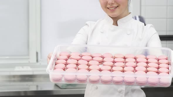 Thumbnail for Cropped Shot of a Pastry Chef Smiling Holding Out Tray with Pink Macaroons