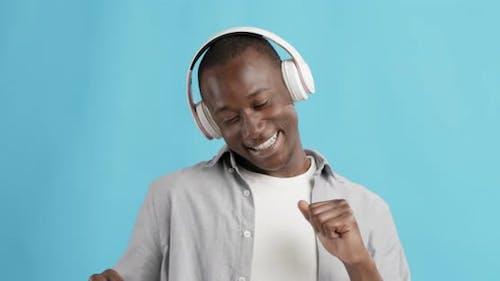 Emotional African American Guy Listening To Music in Headphones