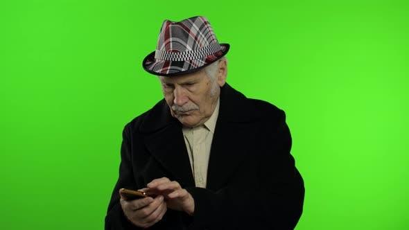 Thumbnail for Elderly Stylish Caucasian Grandfather Man Using Social Media App on Smartphone