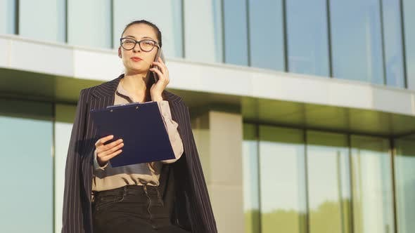 Thumbnail for Portrait of businesswoman with glasses talking at the phone, business building in the background