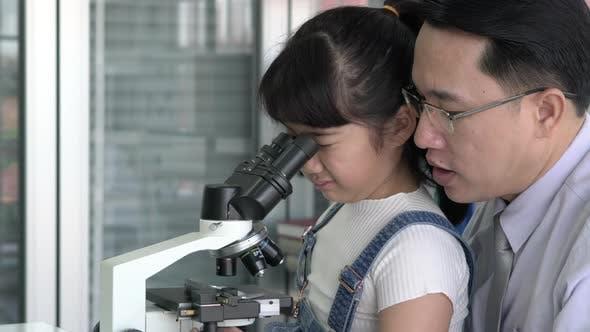 Man and kid girl looking microscope
