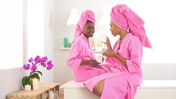 Two African American friends drinking coffee in spa