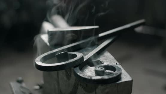 Smoking Forged Metal Rods Lie on the Anvil Next to the Hammer Quench Process Metalwork at Workshop