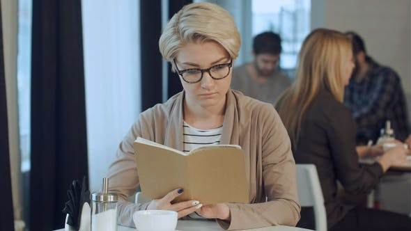 Cover Image for Sunday morning lifestyle scene of young hipster woman reading