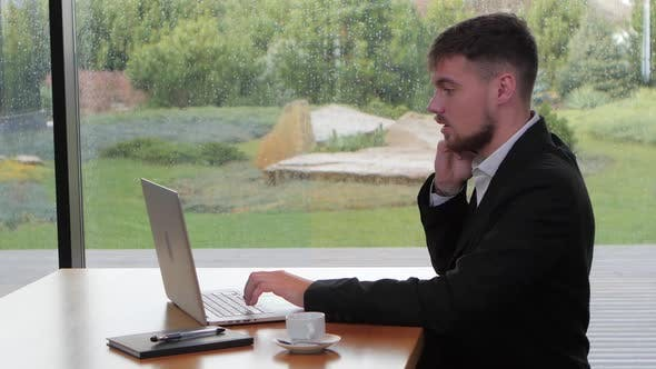 Thumbnail for Businessman Working at His Laptop in a Suburban Cafe