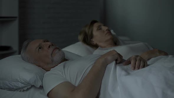 Thumbnail for Elderly Male in Bed Looking at Female Sleeping Near, Turning Back to Her, Fight