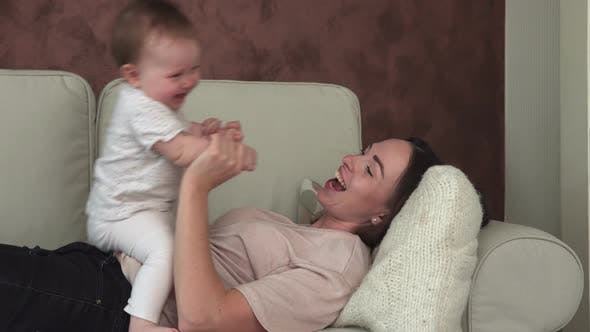 Happy Mother Holding Little Baby By Hand and Kissing on Sofa
