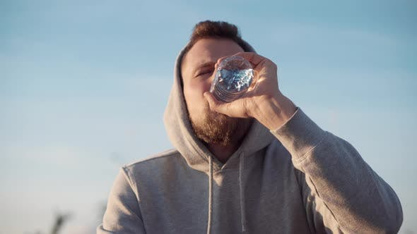 Man Is Tired and Thirsty After Workout