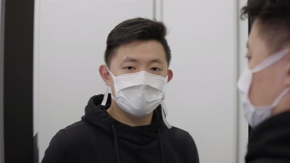 A Young Asian Man in a Face Mask Looks Into a Mirror and the Camera