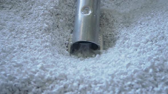 Vacuum Loader Hose Sucking White Virgin Plastic Granules From Tank in Factory Workshop