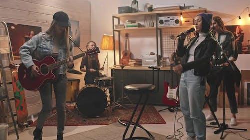 Energetic Girl Band Playing Grunge Music In Studio