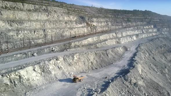 Thumbnail for Aerial View Empty Dump Truck Drives Up To Excavator