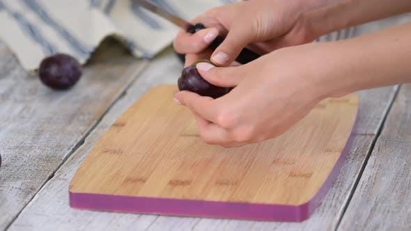 Weibliche Hände schneiden frische Pflaumen mit einem Messer und nehmen einen Knochen heraus