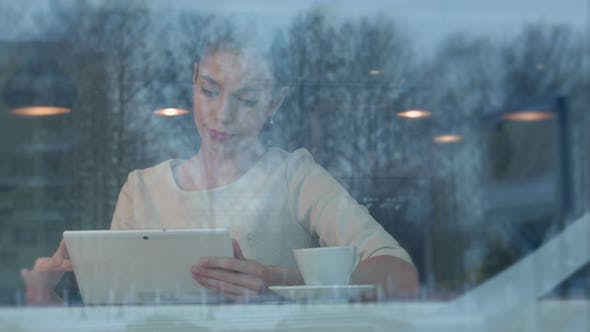 Thumbnail for Happy Young Woman Using Digital Tablet in a Coffee Shop