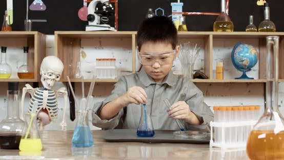 Laboratory Experience in a Chemistry Lesson, Asian Boy in Protective Glasses Pours a Blue Liquid