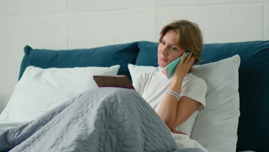 Young Woman Lying in Bed, Talking on Her Smartphone, Using Gadgets