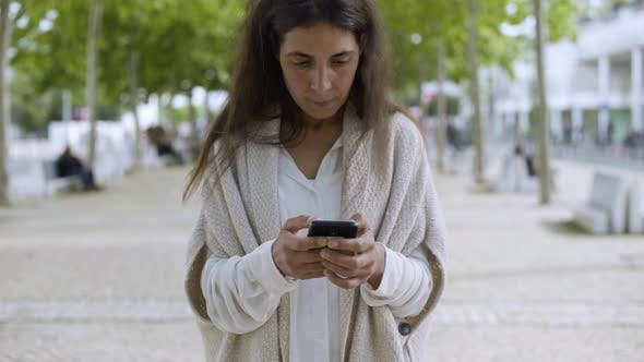 Thumbnail for Smiling Middle Aged Woman Using Smartphone Outdoor